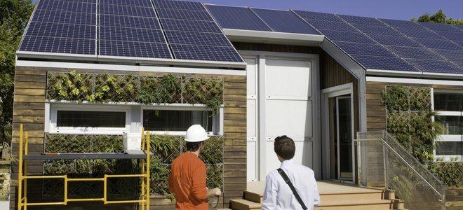 mọi người nhìn vào một ngôi nhà có tấm pin mặt trời trên mái nhà