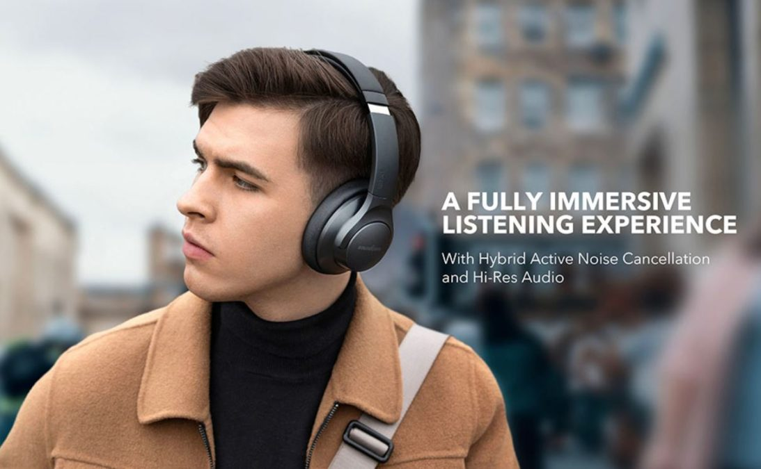 Một người đàn ông đeo tai nghe Bluetooth khử tiếng ồn giá rẻ Anker Soundcore Life Q20.