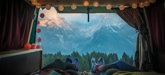 hai người ngồi sau một chiếc xe tải với chuỗi đèn và cửa mở ra núi