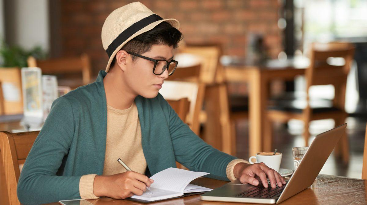 người đàn ông đang học trong quán cà phê trên máy tính xách tay