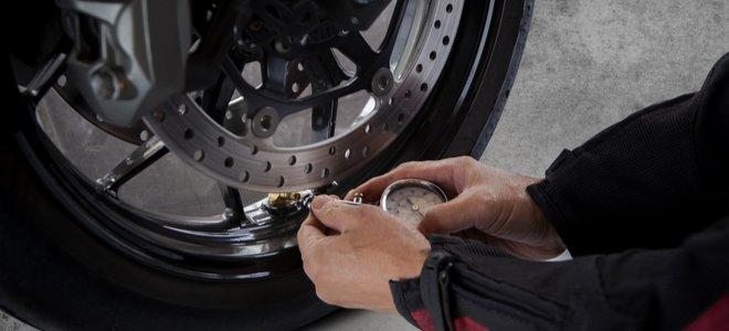 tay kiểm tra áp suất không khí trong lốp xe máy