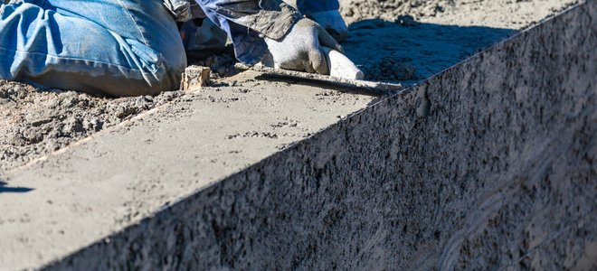 công nhân cạo mép bể bê tông đang xây dựng