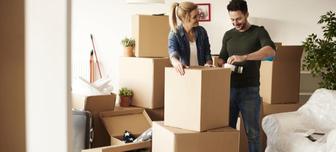 người phụ nữ và người đàn ông đang đóng gói những chiếc hộp lớn và mỉm cười