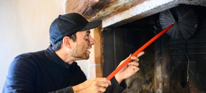 người làm sạch ống khói bằng cách sử dụng bàn chải từ lò sưởi