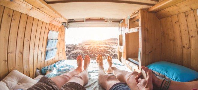 hai chân của người ở phía sau xe tải chở gỗ cắm trại