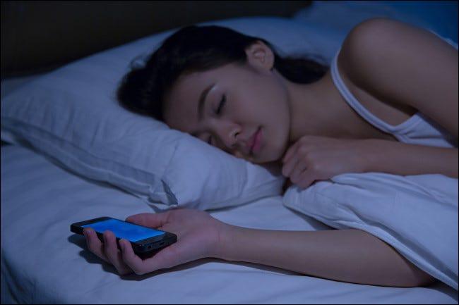 Một người phụ nữ đang ngủ trong khi cầm điện thoại thông minh.