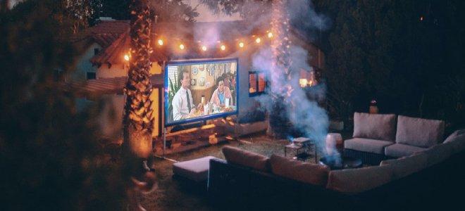 rạp chiếu phim ngoài trời với ghế dài và đèn dây vào ban đêm chiếu phim trên màn hình