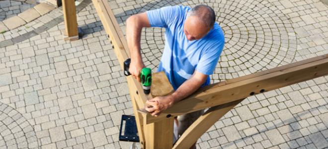 người đàn ông kết nối những miếng gỗ lớn thành một giàn che