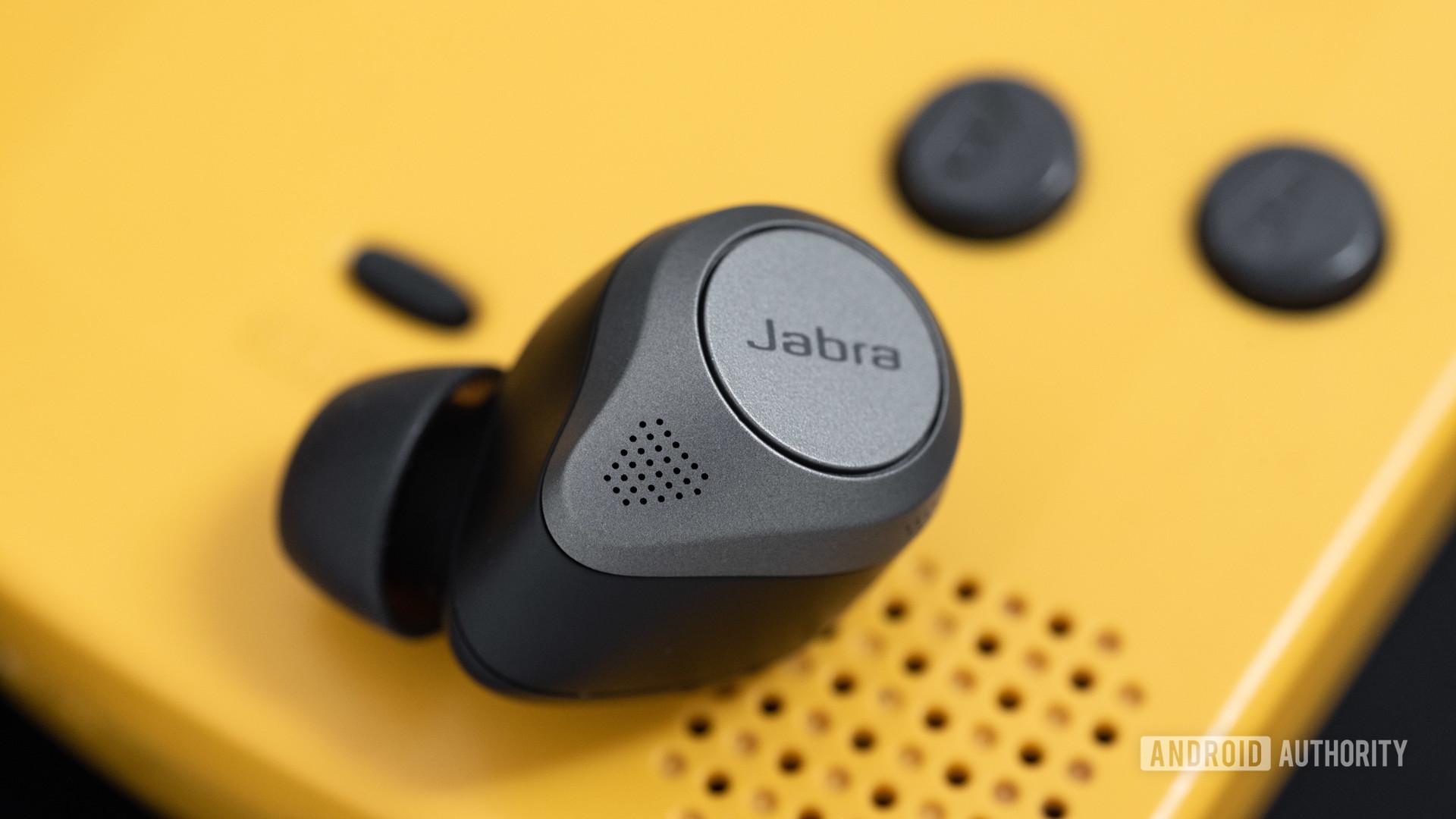 Các lỗ micrô tai nghe không dây thực sự khử tiếng ồn Jabra Elite 85t bên cạnh vỉ loa Gameboy Color.