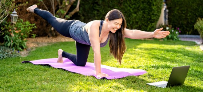 người phụ nữ tập yoga trên thảm trong sân với máy tính xách tay
