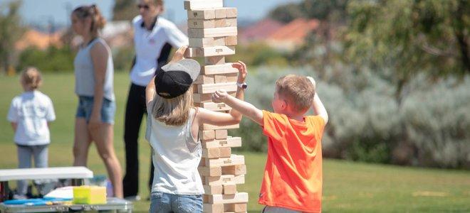 trẻ em chơi trò chơi jenga bằng gỗ lớn ngoài trời