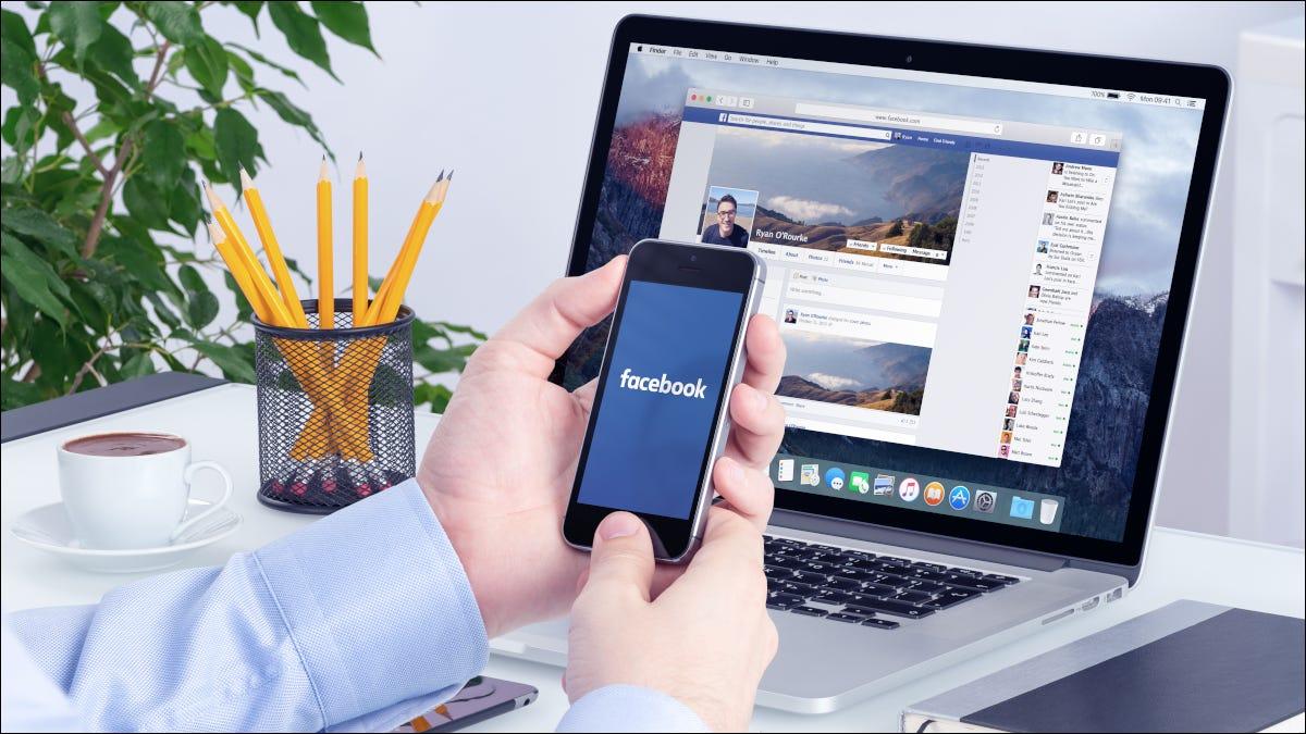 Tay cầm điện thoại thông minh trước máy tính xách tay đang mở Facebook