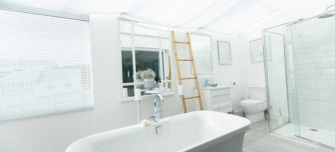 phòng tắm màu trắng với bồn tắm và vòi hoa sen